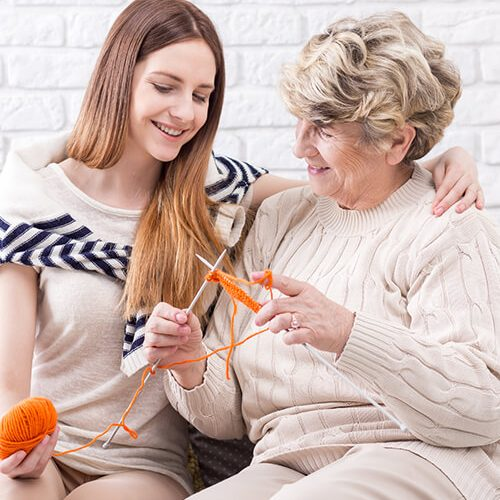 home care services carer with older woman knitting