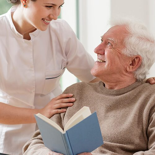 sit-in home care services carer with older man reading book