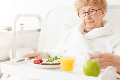 elderly woman getting ready to eat a meal prepared by her carer