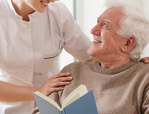 sit-in home care services carer with elderly man reading book