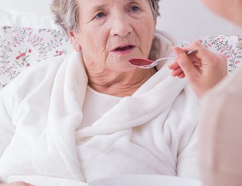 palliative care carer assisting older woman with her meal
